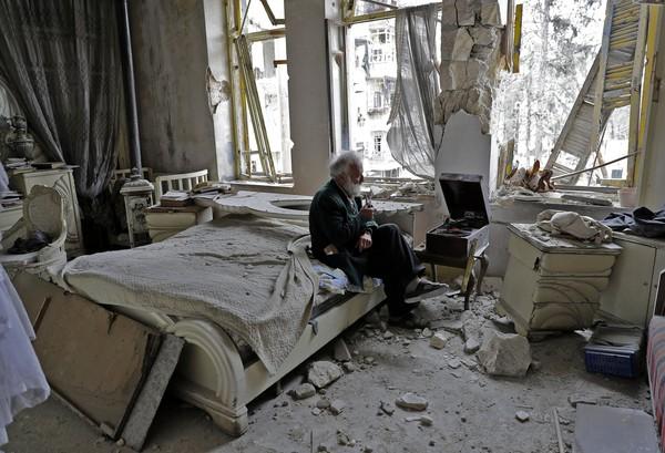 70-летний Мухаммед Мохидэйн Анис курит трубку в своей разрушенной спальне, слушая музыку на своем виниловом плеере в районе аль-Шаар в Алеппо. Фото: Joseph Eid—AFP/Getty Images