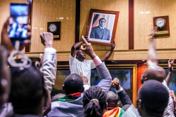 Люди снимают портрет бывшего президента Зимбабве Роберта Мугабе со стены в Международном конференц-центре. Фото: Jekesai Njikizana—AFP/Getty Images