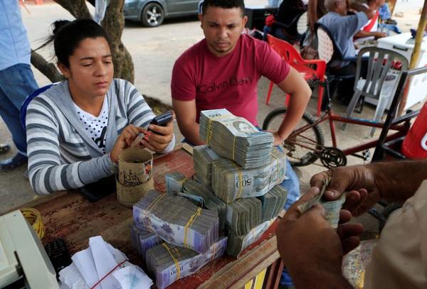 Жители Венесуэлы ходят в магазин с сумками денег