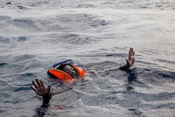 Мигрант пытается сесть в лодку немецкого спасательного патруля в Средиземном море. Фото: Alessio Paduano—AFP/Getty Images